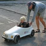 Plac 4. Trampbilen-Lennart Alm. En charmig bild Båda har jätteroligt Fint ljus och skärpa. Pilar och streck på vägen fyller upp vänstra sidan utan att vara störande. En familjebild som även är intressant för utomstående