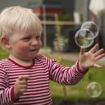 2: Bubbelfångaren-86 Otroligt bra bild, Blicken och glädjen med fokus på bubblorna, möjligen lite hårt beskuren på höger sida, något rörig bakgrund men vi tycker om den, påpassligt tagen och kreativ.