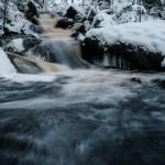 6. Vinterbäcken Benny Larsson       Vatten i mjukt formad rörelse mot oss bildbetraktare nerför fors i vintrigt landskap.  Vackert och tilltalande!