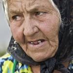 """10. Arne Hurtig - """"Julia Knutas"""" En närbild som visar en människa som har levt ett tag. Gillar utsnittet (beskärning i kameran), man tittar och upptäcker de gnistrande silvriga tänderna, de grå hårstråna som syns tydligt när de framträder framför den mörka huvudbonaden, rynkorna ger karaktär, fint ljus."""