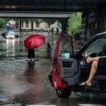) Översvämning – Mats Grimfoot.      Fotografen tycks vara en person som alltid bär med sig sin kamera och passar då på att      fånga ögonblicket. Det är en kul och bra historia i bilden. De röda inslagen (inklusive      kvinnans ben i bilen) leder blicken in i bilden.