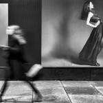 1. Motsatt håll.   Mats Grimfoot       Här har fotografen väntat ut exakt rätt ögonblick för att fånga temat. Det finns också ytterligare      en motsats i bilden; stå & gå. Rörelseoskärpan på den gående personen förstärker budskapet ytterligare.      Genom att bilden är svartvit utesluts distraherande färg som skulle kunna ta uppmärksamhet från bildens      helhet.       En mycket välbalanserad bild       Ett gott arbete i det digitala/analoga mörkrummet.