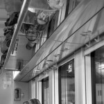 3.  Tågresenärer        Lasse Hallmén        Fotografen har en god blick och ser möjligheten till en bild i det vardagliga som uppfyller temat på ett annorlunda sätt.        Kompositionen är bildens styrka. Informationen i spegelbilden avslöjar vad som pågår i stolarna.        Fina gråtoner. Återigen ett gott arbete i det digital/analoga mörkrummet.